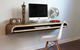 floating monitor desk with wood finishing top desk and sliding additional panel underneath casual white chair a decorative clock a red car miniature globe miniature a flat-screen computer
