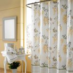 floral patterns in shower curtain a white console table with bathing supplies and towel square decorative mirror with white frame