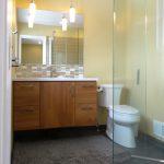Frameless Sliding Door For Bathroom Wood Bathroom Vanity With White Top Glossy Tiles For Backsplash Two Pendant Lamp Fixtures A Closet Unit Dark Large Subway Tiles Floor