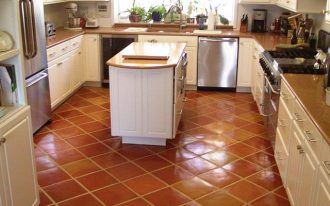 glossy brown tiles kitchen flooring centered- kitchen island with drawers and wood top luxurious kitchen set with modern appliance