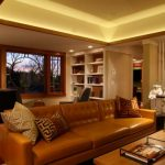 gorgeous living room design with rectangular brown leather sofa and ravishing ceiling lamp with unique semi round window elaborate with small office in laminate flooring