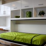 green mattress folded-bed unit with  mini desk and single cabinet on the left and shelving unit and cabinetry on top