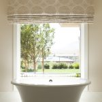 large Roman shade with beautiful pattern and color small and deep tub fixture white-frame opened window