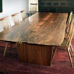 large dining table with wood-finish top for 12 persons six wood dining chairs red carpet for dining room