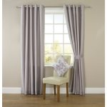 light-purple floor to cealing window curtains  a casual white chair with a beautiful ornamental pillow