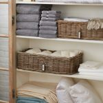 linens closet shelves made from wood two rattan baskets with name-tags piles of linens based on categorizations  bed sheet sets bec coverings  pillows