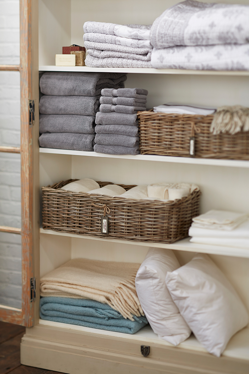 Linens Closet Shelves Made From Wood Two Rattan Baskets With Name Tags  Piles Of Linens