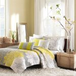 luxurious bedding from Cynthia Rowley big-flower patterns in white and yellow tones thick soft white fury carpet rattan box for storage minimalist large clear glass vase with vivid flowers ornament