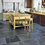 luxurious black tiles flooring in kitchen gold-tone kitchen island with wood top  single chair bar in gold-accent  gold-color kitchen countertops and  dark-wood top and under cabinetry