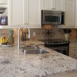 luxurious kitchen set with white-dominant cashmere granite for top kitchen island double sinks with a single stainless steel faucet a dish of fuits some modern kitchen appliances