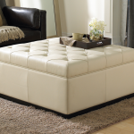 luxurious white storage Ottoman comfy and elegant black leather-coat sofa a wool blanket smooth and soft light grey fury carpet brushed- wood flooring