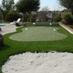 medium-size putting green for golf with some golf balls and flags  a smooth sands area near putting green zone a luxurious and large outdoor pool a pool furniture