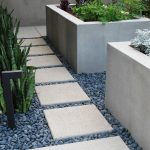 minimalist home garden idea with medium-size concrete planter boxes for growing plants and fabricated natural stone walk-way feature