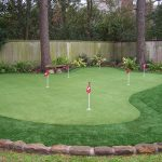 minimalist putting green for playing golf with red flags surrounded by old lattice fence system