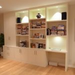 minimalist wall unit for shelves unit and storage with desk piles of books collections  twin sound system units on top some pictures frames on shelf solid wood floors
