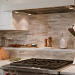 minimalits groutless kicthen backsplash with excellent lighting  modern gas stove fixture a book recipe some spacy containers a knife stand casual white top cabinet system