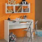 modern minimalist student desk in white with white floating bookshelf transparent lucite folding chair a bright blue foot mat  bright orange wall paint
