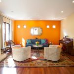 orange painted wall creame painted wall blue sofa beautiful patterned rug old wooden piano colorful cushion gray cozy armchair round wooden coffee table amazing moroccan living room