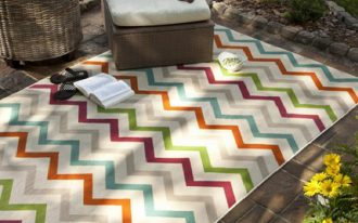 outdoor jaunty rug with multicolor a single seat with rattan base rattan round table with plant ornament an opened book