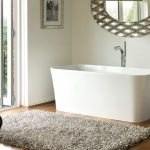 oval-shape ornamental mirror with beautiful frame medium-size tub with water tap feature grey thick fury carpet laminated wood finish floor movable cart for bathing properties large glass door