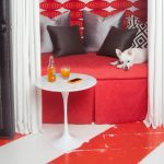red and white solvent-based floor epoxy paint  comfy daybed in red color with neautral-colored pillows a cute puppy minimalist white round table with beverage