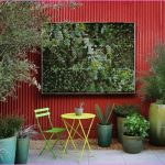 red outdoor fence system with large nature painting in silver frame some decorative pots with their fresh and vivid plant ornaments a single chair and table set for patio
