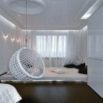 round basket hanging chair in white color darkwood flooring large white carpet with smooth and soft surface  transparent white window curtains