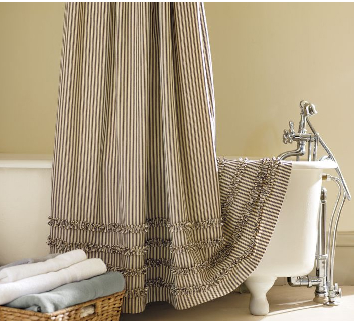 shower curtain with tiny vertical strips patterns a large white bathtub with flawfeet a rattan basket