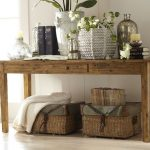 simple and rustic console table with a lot of decorative items two rattan boxes as the storage under table