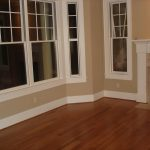 simple baseboard design brushed wood floors  a fireplace mantel glass window group with white frames