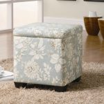 simple storage Ottoman with white floral pattterns in blue comfy and warm fury carpet wood-laminate floor some interior ornaments  a white coffee cup