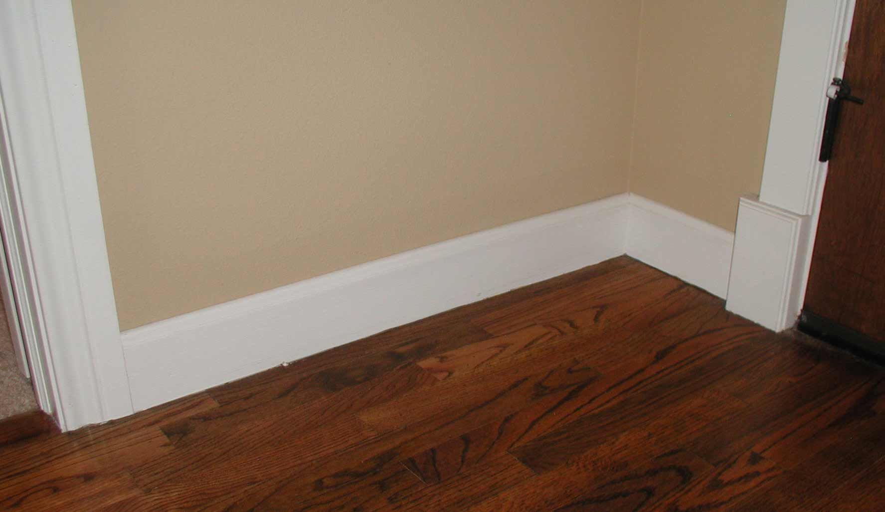 Simple White Baseboard Laminate Wood Floors With Clear Lines