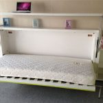 single folded-bed idea with bookcases and cabinet on left and right sides some books collections and picture frames and also a unit of laptop