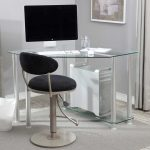 small corner desk with transparent glass panel a set of monitor a keyboard wireless mouse comfy office chair with black seating and black back features