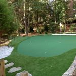 small putting green for golfing with single white flag feature large stone arrangement for walkway in the backyard
