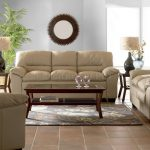 soft brown sofas for living room a side-tables with table lamps floral patterned carpet brown tiles floor beautiful round mirror ornament on the wall
