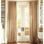 soft brown window curtains for French door  built-in shelves for storage many rattan boxes as the decorative items and storage units