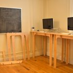 standing desk for monitor made from softwood material two flat-screen computer units a blackboard some cardboards  brushed-wood floor