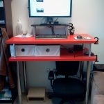 standing  workstation with double layered-red panels a computer unit with keyboard and mouse a black office chair with wheels