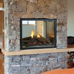 three sided  gas fireplace with natural stone wall system