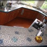 tile countertop with small and big patterns a built-in electric stove square white sink and faucet many containers and  decorative kitchen stuffs wood finishing floor