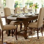 timber dining table in classic style big and luxurious dining chairs  several wine glasses and dishware brown carpet with big flower patterns a flower arrangement as dining table decoration