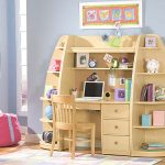 unique and creative wood shelving and storage with desk and mini cute chair for kid a laptop unit on the desk  some cute decorative items some picture frames sweet wall decorations  cozy chair in pink color