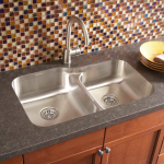 vinyl countertop with double deep stainless steel sinks and single faucet a pile of small flat plates small mosaic tiles for backsplash