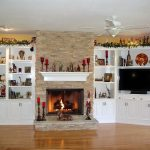 white built-in cabinets and shelves around the fireplace mantel in Christmas decoration a giant electric ceiling fan wood finish floor
