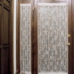 white lace sidelight window curtain in darkwood-framed main door a flower decoration