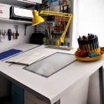 white minimalist drafting table Ikea with small glass panel and under storage a unique yellow table lamp scissors hang-kit unique drafting tool container