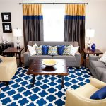 white painted wall eyecatching blue and white rug creame leathered armchairs gray sofa colorful curtain wooden coffee table colorful cushions stunning moroccan living room