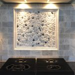 white-washed tiles backsplash with a frame containing white and black river rock decorations four sets of modern gas stoves modern lighting fixtures