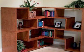 wide corner bookshelves unit in wood material  book arrangements some pictures with black frames  ceramic beige floor flowrer ornament